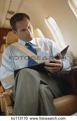Stock Photography of Businessman reading on private plane.