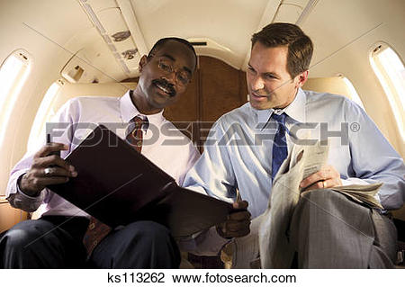 Stock Photo of Two businessmen reading on private plane. ks113262.