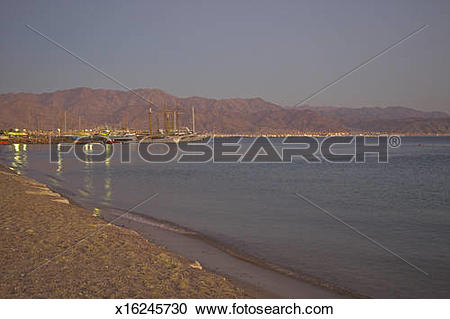 Stock Photography of Curve of Red Sea shoreline with boats at.