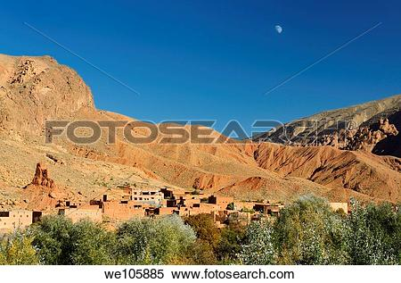 Stock Image of Moon in blue sky over red soil and rock formations.