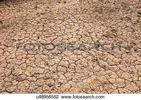 Stock Photo of Dry cracked red soil u48956552.
