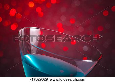 Stock Photograph of detail of one glass blue cocktail on red tint.