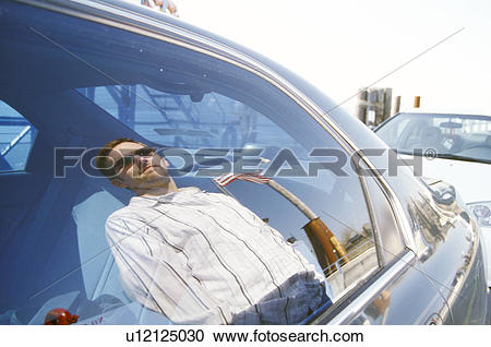 Stock Photography of Man and Flag Reflected in Car Window.