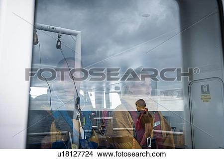 Stock Photo of Captain and female scientist reflected in window on.