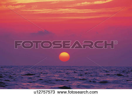 Stock Photo of the Sun Going Down at Sea, the Sky Reflecting the.