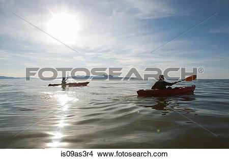 Stock Photo of Couple kayaking, sunlight reflecting on water.