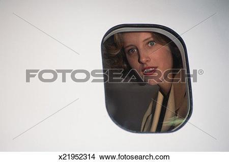 Stock Photo of Woman looking out through airplane window, view.
