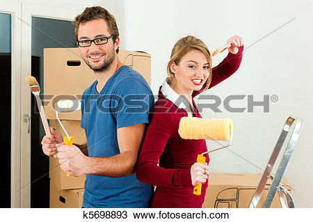 Stock Photo of Young couple moving in a home or apartment, they.