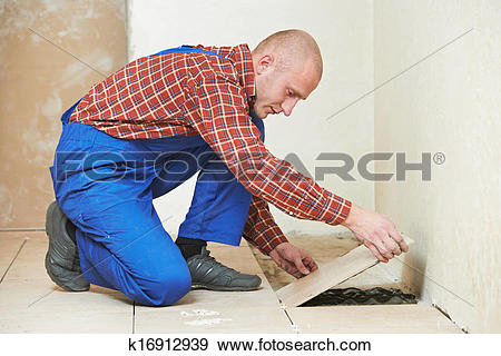 Stock Photograph of tiler at home floor tiling renovation work.