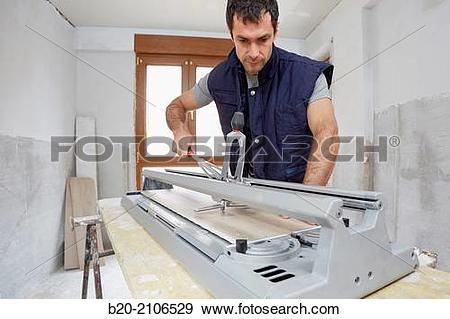 Stock Photograph of Bricklayer cutting tile. Manual tile cutter.