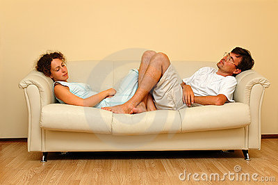 Woman And Man Repose On The White Sofa Stock Images.