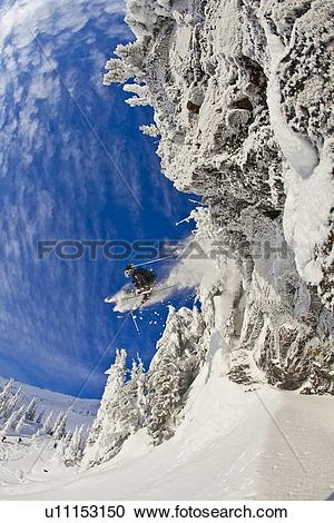 Stock Photography of A male skier catches some air off a cliff in.