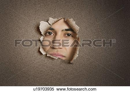 Stock Image of Portrait of a young Indian man peeking from ripped.