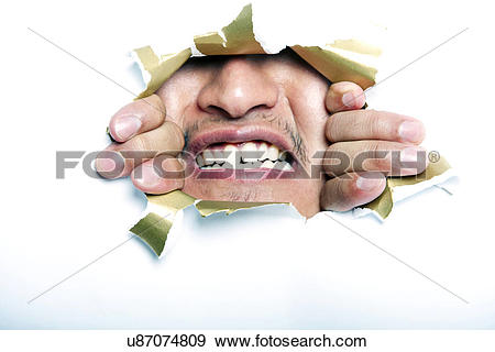 Stock Photograph of Young Korean man looking through ripped paper.