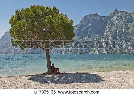 Stock Image of Woman sitting in tree shade, Lake Garda, Riva Del.