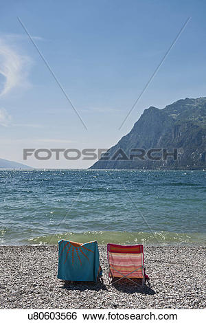 Stock Images of Pair of empty deckchairs with beach towels, Lake.