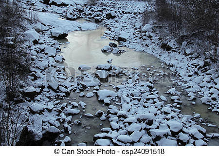 Stock Photography of Frozen riverbed with snowy rocks in winter.