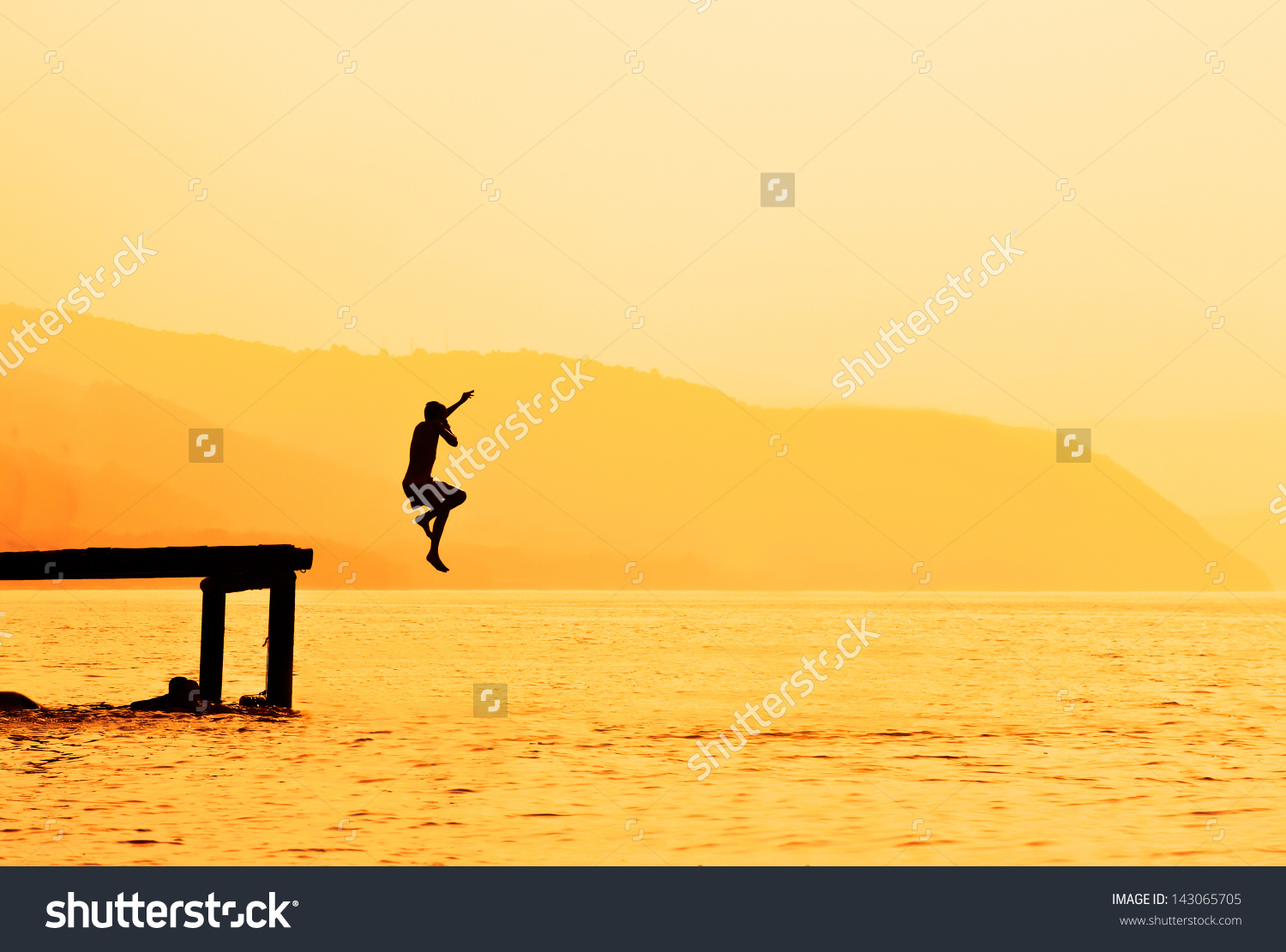 Silhouette Of Kids Jumping From River Dock, At Sunset. Stock Photo.