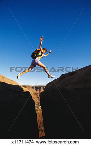 Stock Photo of Young woman jumping over rock crevice, low angle.