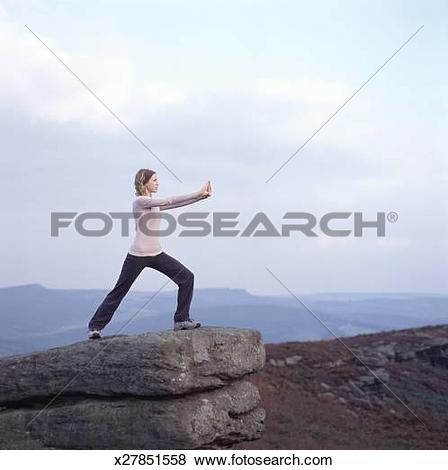 Pictures of Young woman practicing yoga on rock edge x27851558.