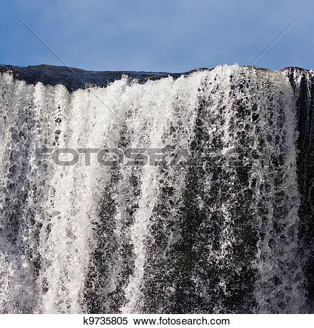 Stock Image of Water cascading over rock edge forming a waterfall.