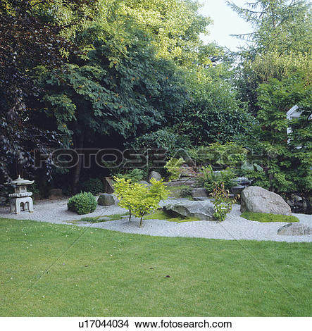 Stock Photo of Oriental rock garden with raked gravel in front of.