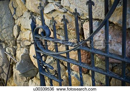 Stock Images of Cast iron gate open against rock wall u30339536.