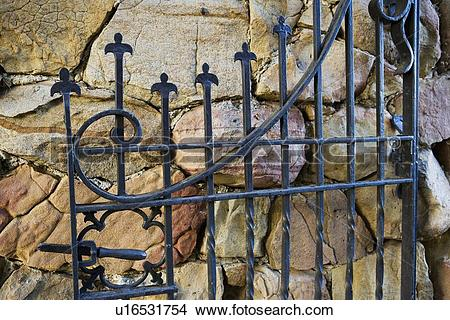 Stock Photo of Cast iron gate open against rock wall u16531754.