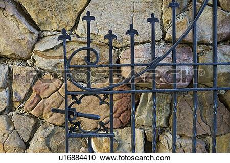 Stock Photography of Cast iron gate open against rock wall.