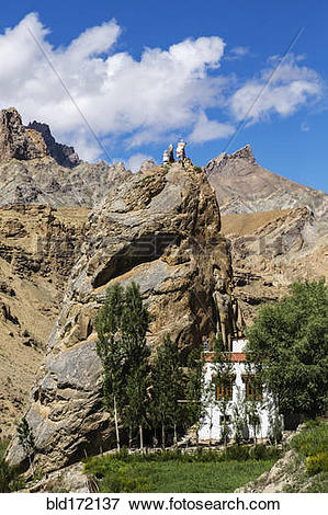 Picture of Buddha statue on rock formations in remote landscape.