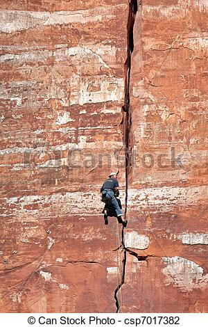 Stock Photo of Man climbing sheer rock face in Zion National Park.