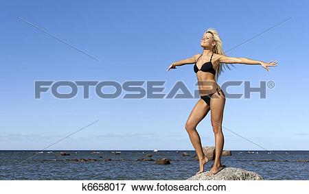 Picture of girl in bikini posing on a rock near the sea k6658017.