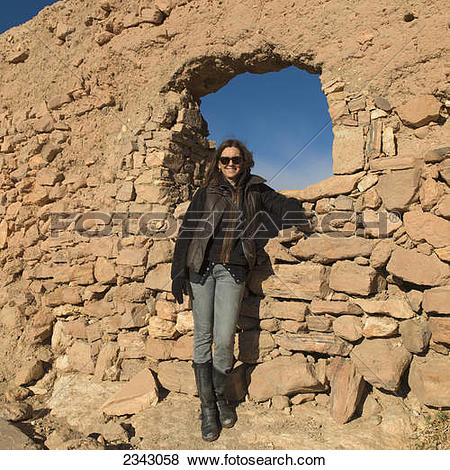 Pictures of A woman posing by a rock wall with a window; Ait.