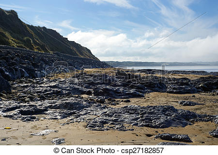 Stock Images of calm day over the black rock shore.