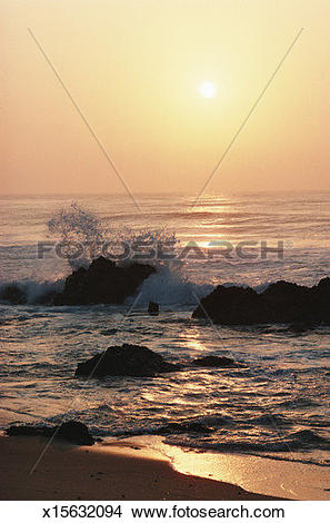 Stock Photo of Waves breaking on rocks and surf washing over beach.