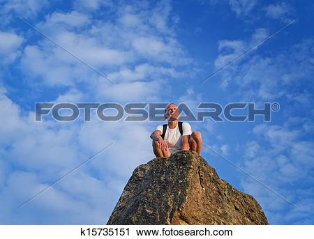 Stock Photography of Man sitting on top of a rocky pinnacle.