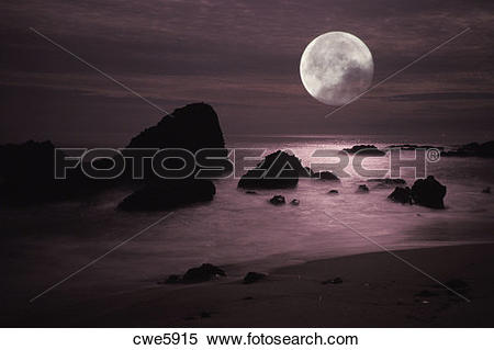 Stock Image of Moonset over rocky shore in Laguna Beach California.