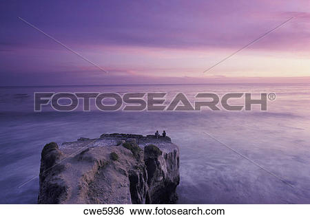 Stock Images of Couple sitting on rocky pinnacle over Pacific.
