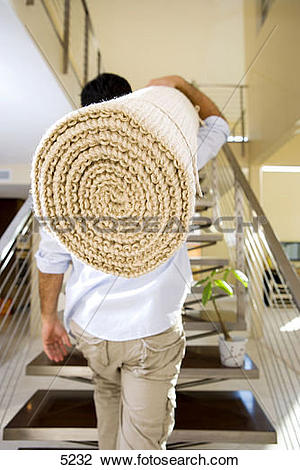 Stock Photo of Man moving house, carrying rolled.