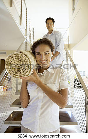 Stock Photo of Couple moving house, carrying rolled.
