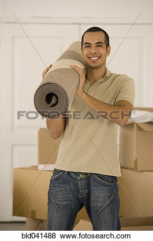 Pictures of Man holding rolled rug in new house bld041488.