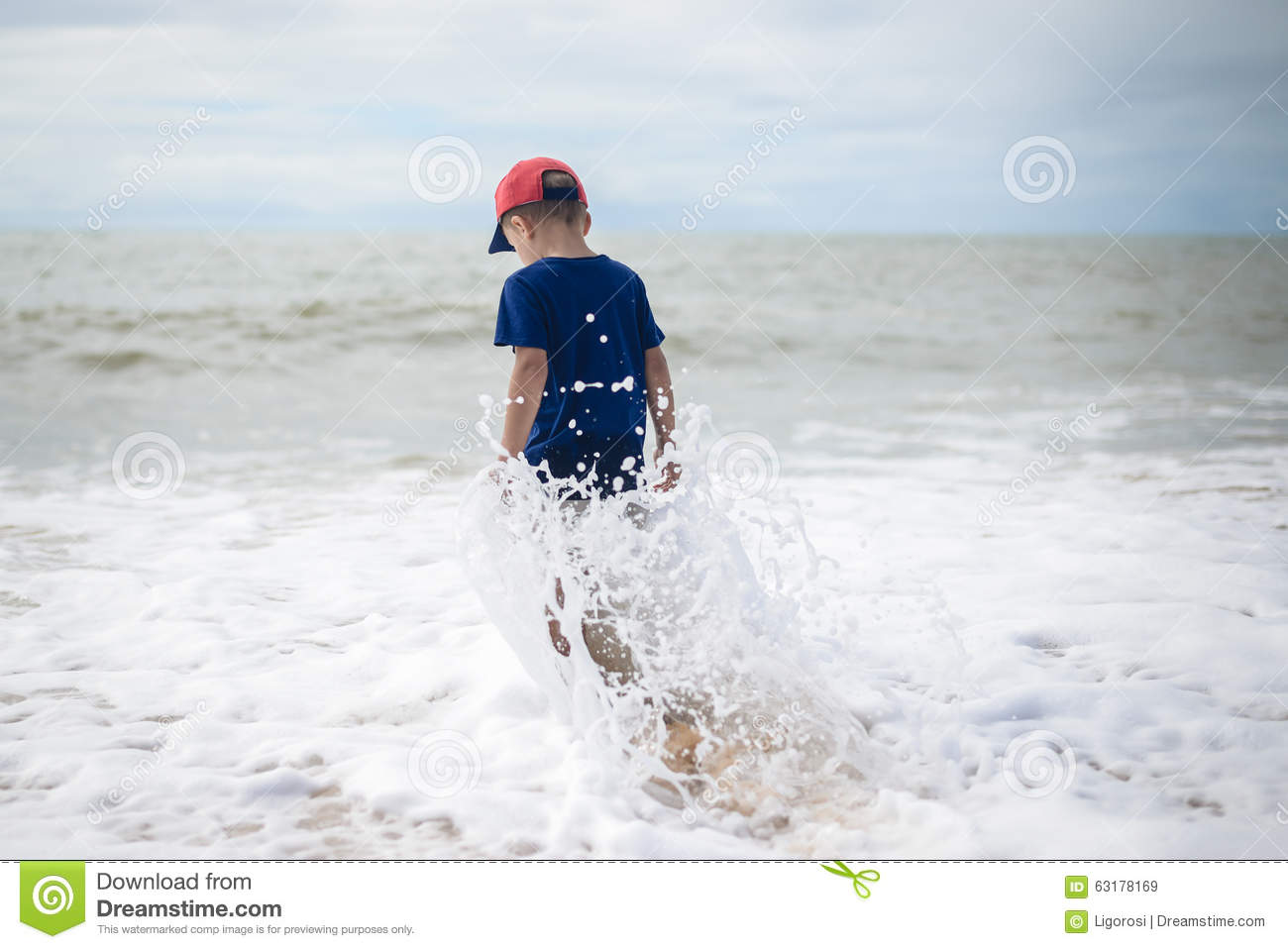 Small Brave Boy Going To Swim In Rolling Sea Alone Stock Photo.