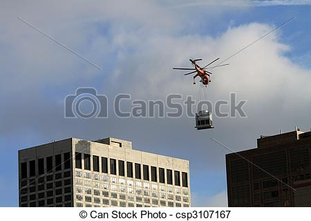 Picture of A helicopter placing some heavy equipment on the roof.