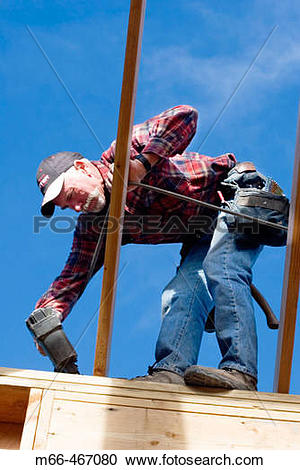 Stock Photography of Carpenter standing on top of a wall, nailing.