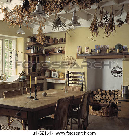 Picture of Dried herbs and hops on beams above antique pine table.