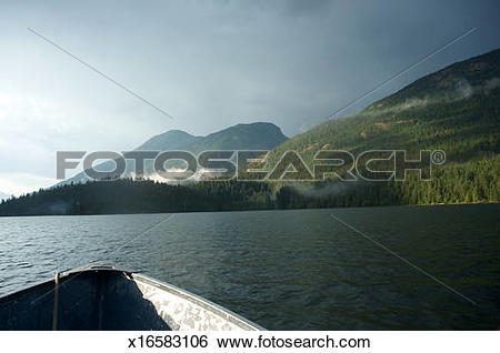 Stock Images of In a boat floating on Ross Lake at sunset.