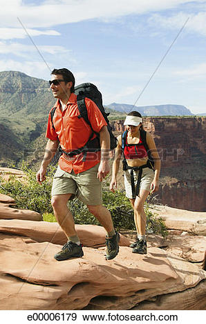Stock Photograph of Backpacking couple hiking on rough terrain.