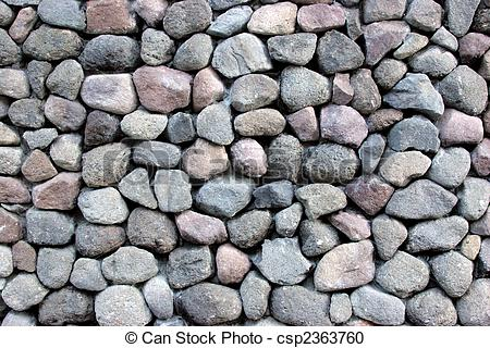 Stock Photography of Round rocks stacked outside.