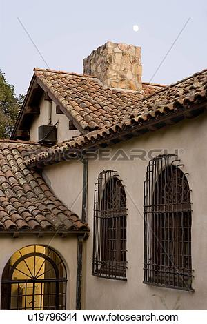 Stock Photo of Row of windows with wrought iron grills on side of.