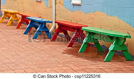 Stock Photography of Primary Colored Benches in Row on Bricks.